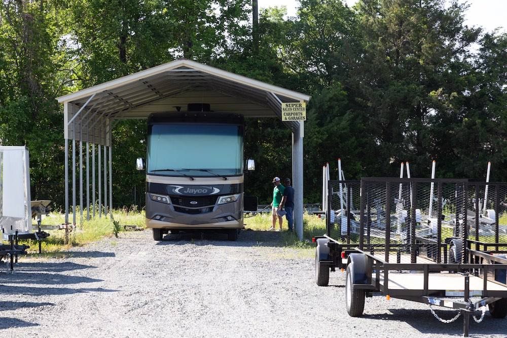 large carport with recreational vehicle underneath and boat trailers to the right